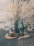 De de glaskruik en kop thee op houten lijst verfraaien met droge bloemen Stock Afbeeldingen