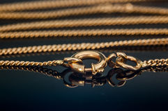 De de gouden die greep of sluiting van de halsbandketting bij het wijzen van glas op lijst wordt gesloten Stock Foto