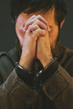 De de handboeien om:doen mannelijke gevangene in militaire eenvormig bidt Stock Foto