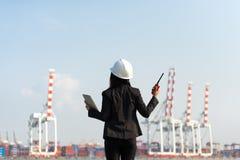 De de holdingsradio van de vrouweningenieur en het werken met de vrachtschip van de containerlading in scheepswerf bij schemer vo Stock Foto's