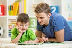 De de jong geitjejongen en vader lezen een boek binnen op vloer Stock Afbeeldingen
