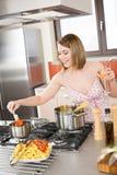 De de kokende spaghetti en tomatensaus van de vrouw stock foto