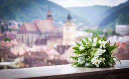 De de lentebloemen van het huwelijksboeket met Brasov-stad bekijken panoramisch stock foto