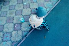 De de lentedag op de van de de babyjongen van het Speelplaatsasfalt de het jasjehoed en tennisschoenen trekt met krijt van versch Stock Fotografie