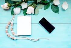 De de lentelay-out op een blauwe houten achtergrond met bloemen en nam de bladen van de bloemblaadjesblocnote voor nota's en tele Royalty-vrije Stock Foto's