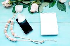 De de lentelay-out op een blauwe houten achtergrond met bloemen en nam de bladen van de bloemblaadjesblocnote voor nota's en tele Royalty-vrije Stock Afbeeldingen