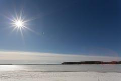 De de lentezon in de middag over het meer met ijs wordt behandeld dat Stock Afbeeldingen