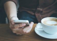 De de mobiele telefoon en koffie van het zakenmangebruik kop donkere toon Royalty-vrije Stock Foto