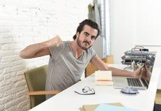 De de moderne student of zakenman die van de hipsterstijl in spanning werken met laptop thuis verstoorde bureau boos Stock Foto