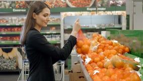 De de mooie vrouwen het winkelen groenten en vruchten in supermarkt, brunette kiezen tomaat en peper, verse salade stock foto