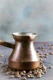 De de oude pot en bonen van de koperkoffie op donkere rustieke achtergrond Stock Afbeeldingen