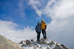 De de paarman en vrouw die zich bovenop een sneeuwberg bevinden Royalty-vrije Stock Afbeelding