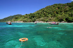 De de reddingsboeiring en reizigers genieten van snorkelend in duidelijk water Stock Fotografie