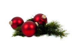 De de rode ornamenten/snuisterijen van Kerstmis met pijnboomtak Stock Afbeelding