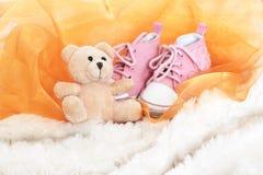 De de roze schoenen en teddybeer van de baby Stock Foto