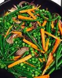 De de slabonenerwten en wortelen bewegen gebraden gerecht Stock Foto's