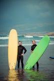 De de surferbeginner en instructeur op een strand met het surfen schepen in Stock Foto's