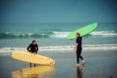De de surferbeginner en instructeur op een strand met het surfen schepen in Stock Afbeeldingen
