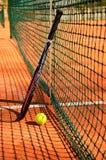 De de tennisbal en racket zijn dichtbij de netto verticaal royalty-vrije stock foto's