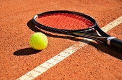 De de tennisbal en racket zijn horizontaal op het tapijthof Royalty-vrije Stock Fotografie