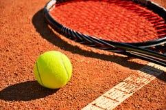 De de tennisbal en racket zijn op de close-up van het tapijthof Royalty-vrije Stock Foto