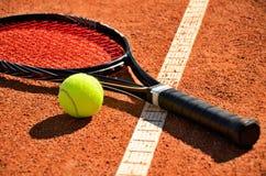 De de tennisbal en racket zijn op het tapijthof Royalty-vrije Stock Afbeeldingen