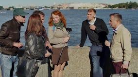 De de toeristengroep en gids die op dijk op achtergrond van grote rivier bespreken schoten met driepoot stock videobeelden