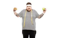 De de vette hamburger en appel van de mensenholding met gelaatsuitdrukking Royalty-vrije Stock Fotografie