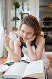De de vrouwenlezing en holding een koffie vormen tot een kom Stock Fotografie