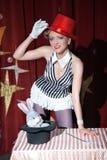 De de vrouwentovenaar van de circuskunstenaar toont magische truc Stock Foto