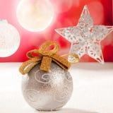 De de zilveren snuisterij en ster van Kerstmis op sneeuwrood Stock Foto's