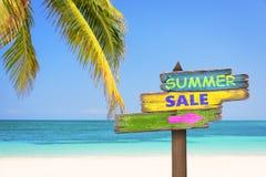 De de zomerverkoop op pastelkleur wordt geschreven kleurde houten richtingstekens, strand en palmachtergrond die stock fotografie