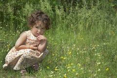 In de de zomerzitting op een krullend peinzend meisje van de bloemweide Stock Afbeelding
