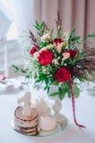 De decoratie van de huwelijksceremonie in restoraunt De samenstelling van rode en roze bloemen, groene tribunes op lijst met wit  Stock Foto