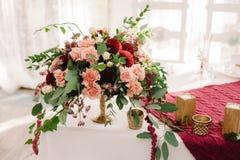 De decoratie van de huwelijkslijst met de rode en roze bloemen op de witte doek royalty-vrije stock foto