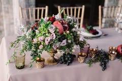 De decoratie van de huwelijkslijst met de roze bloemen, de granaatappel en het groen stock afbeeldingen