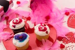 De decoratie van de valentijnskaartendag en cupcakes met hart gevormde frosti stock foto's