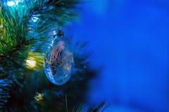 De decoratie van de kerstboombal het hangen op nette die tak door feestelijke lichten wordt omringd Ruimte voor tekst stock afbeeldingen