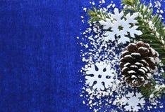 De decoratie van Kerstmis De witte sneeuwvlokken en de sneeuwspar vertakken zich en denneappel op blauwe achtergrond met copyspac Stock Foto's