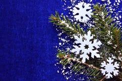 De decoratie van Kerstmis Decoratieve gevoelde sneeuwvlokken en sneeuwsparrentak op blauwe achtergrond met copyspace Stock Afbeelding