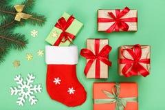De decoratie van Kerstmis De laars van de kerstman, giftdozen, spar vertakt zich met kegels en decoratieve snowflackes op groene  royalty-vrije stock afbeelding