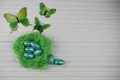 De decoratie van de lentepasen met met de hand gemaakt groen die kleurennest met de blauwe glanzende folieeieren en decoratie van royalty-vrije stock afbeeldingen