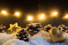 De decoratie van de winterkerstmis met het gouden hart gevormde ornament en de denneappels van de Kerstmisboom stock afbeeldingen