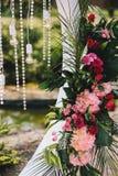 De decoratieclose-up van de huwelijksboog Bloemboeketten van palmbladen, roze en rode rozen, gloeilampen en kristallen stock afbeelding