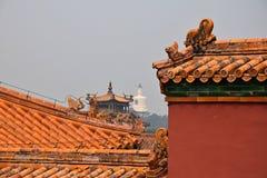 De decoratieve daken van Verboden Stad met de Witte pagode in Beihai-park op de achtergrond, Peking, China royalty-vrije stock afbeelding