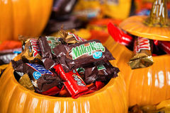 De decoratieve die pompoenen met geassorteerde Halloween-chocolade worden gevuld kunnen Stock Afbeelding