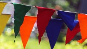 De decoratieve driehoekige vlaggen van partij multicolored gestreepte wimpels op een twee kabel, close-up stock fotografie