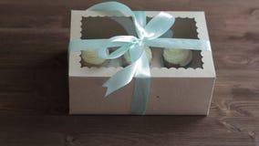 De decoratieve giftdoos bond met cupcakes een turkoois lint in vrouwelijke handen stock footage
