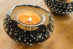 De decoratieve houders van de glaskaars met aangestoken kaarsen die zich op een lijst in de woonkamer bevinden Royalty-vrije Stock Afbeelding