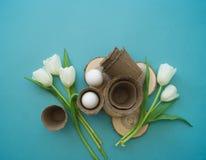 De decoratieve samenstelling van Pasen op een blauwe achtergrond Wit konijn, tulpen, bloempotten, unpainted eieren en een boom Royalty-vrije Stock Afbeeldingen